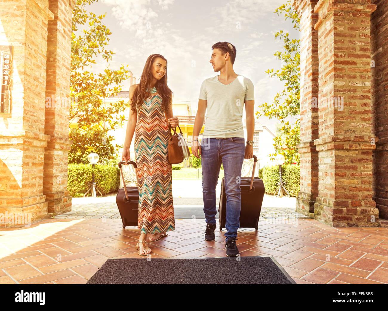 Pareja joven de pie en el pasillo del hotel a la llegada, buscando habitación, sosteniendo las maletas Imagen De Stock