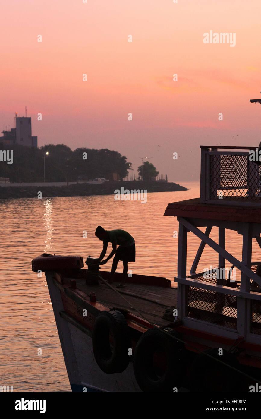 La India, Maharashtra, Mumbai, Colaba distrito, hombre silueteado en el barco en el puerto de Mumbai, cerca de la Imagen De Stock