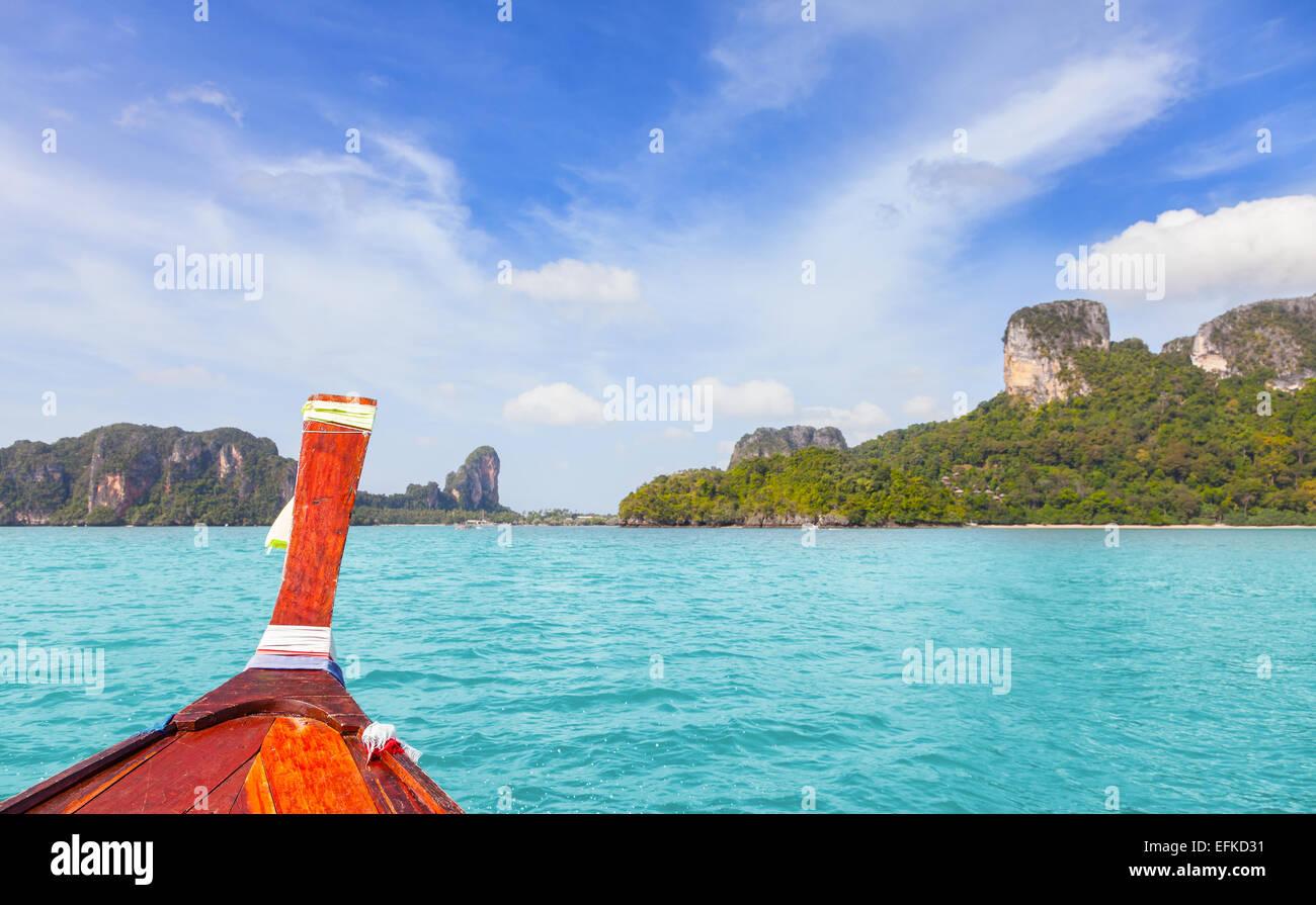 Barco de madera y una isla tropical en la distancia. Imagen De Stock
