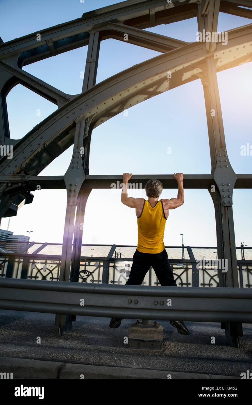 Hombre haciendo chin-ups en el puente, Munich, Baviera, Alemania Imagen De Stock