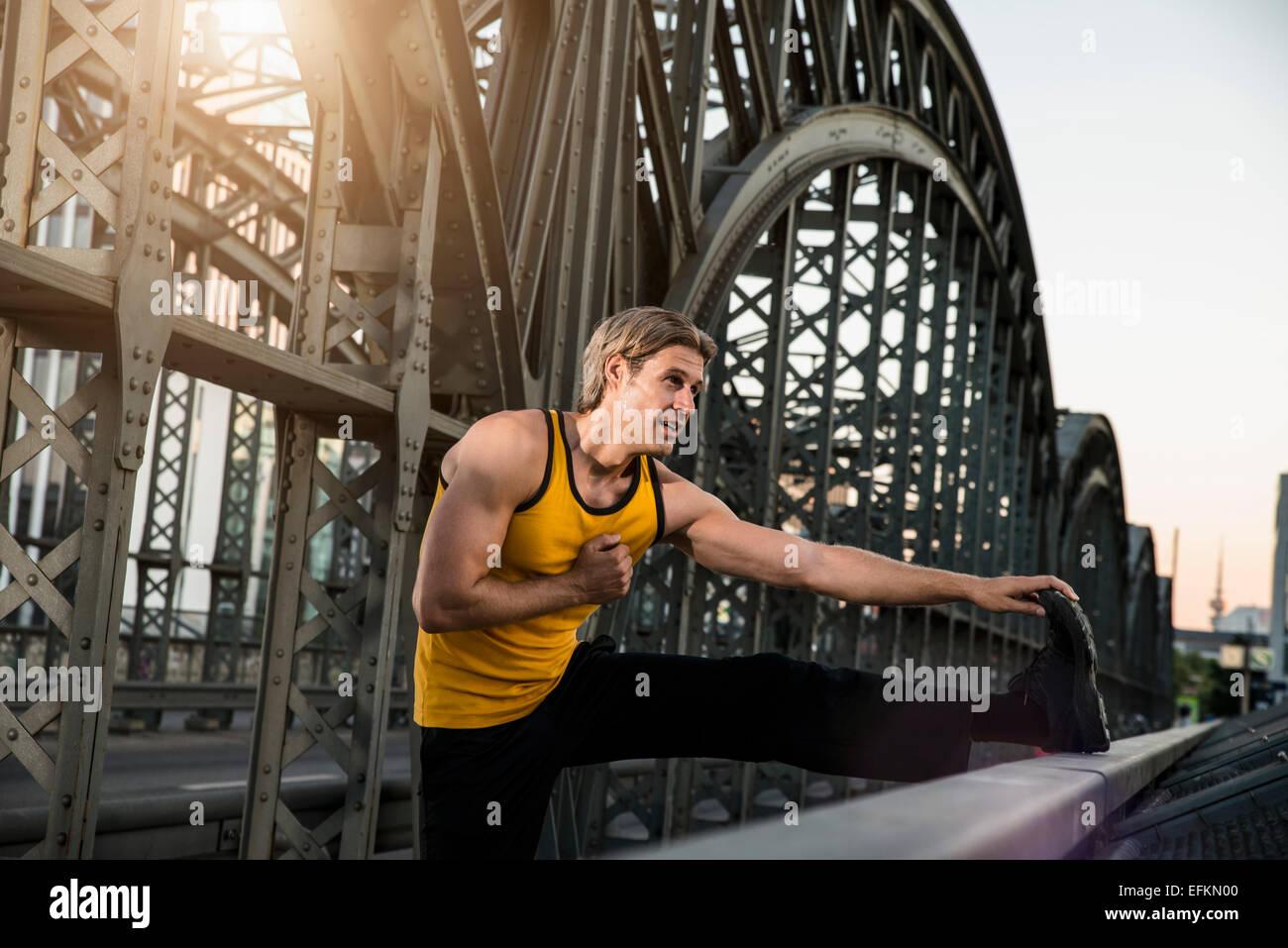 Hombre pierna estiramiento en el puente, Munich, Baviera, Alemania Imagen De Stock