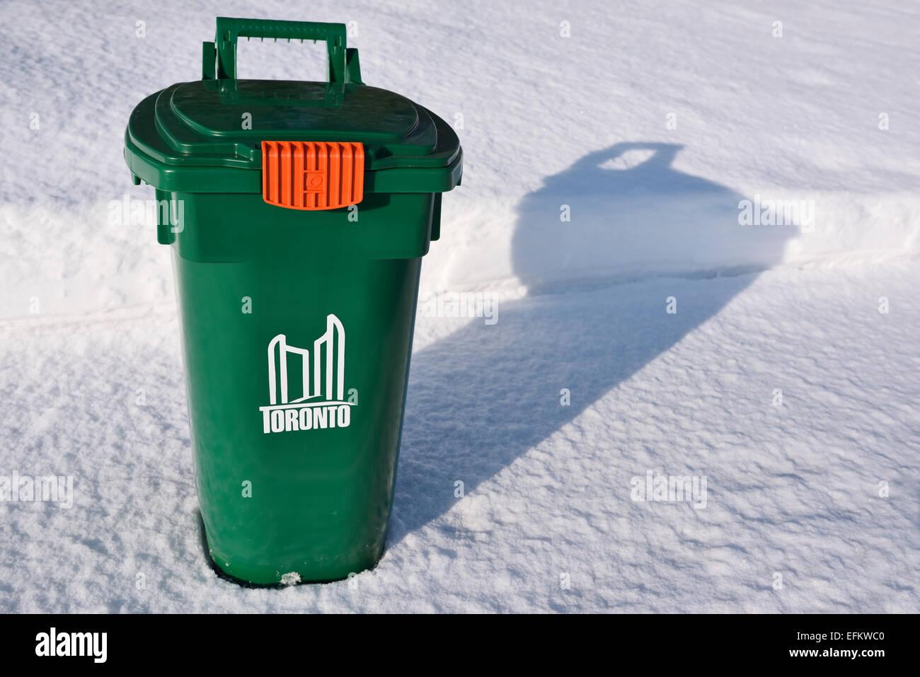 Nuevo contenedor verde de reciclaje de Toronto en la acera cubierta de nieve fresca en invierno Imagen De Stock