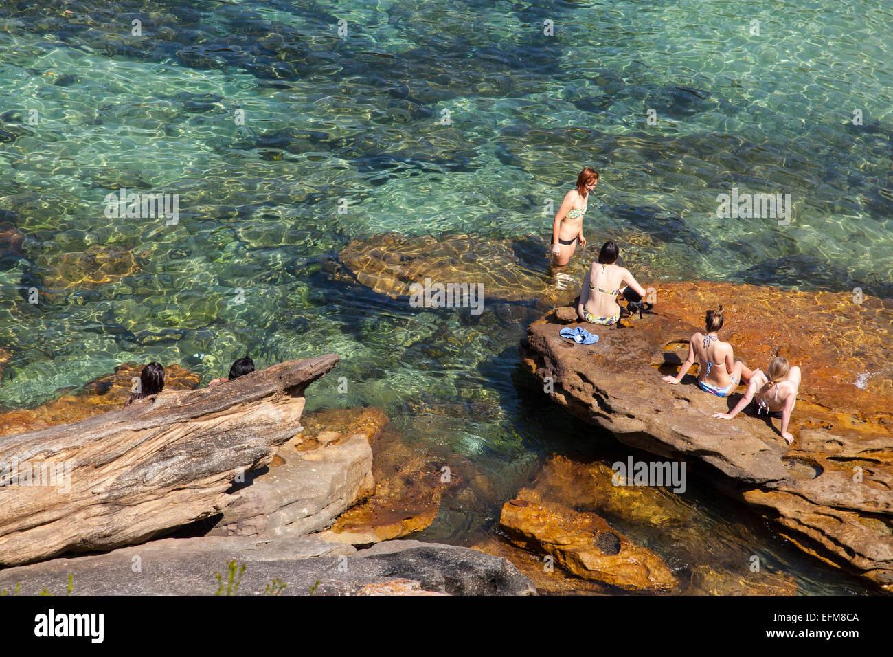 Mujer sentada sobre una roca en Gordon's Bay, Sydney, Australia. Imagen De Stock