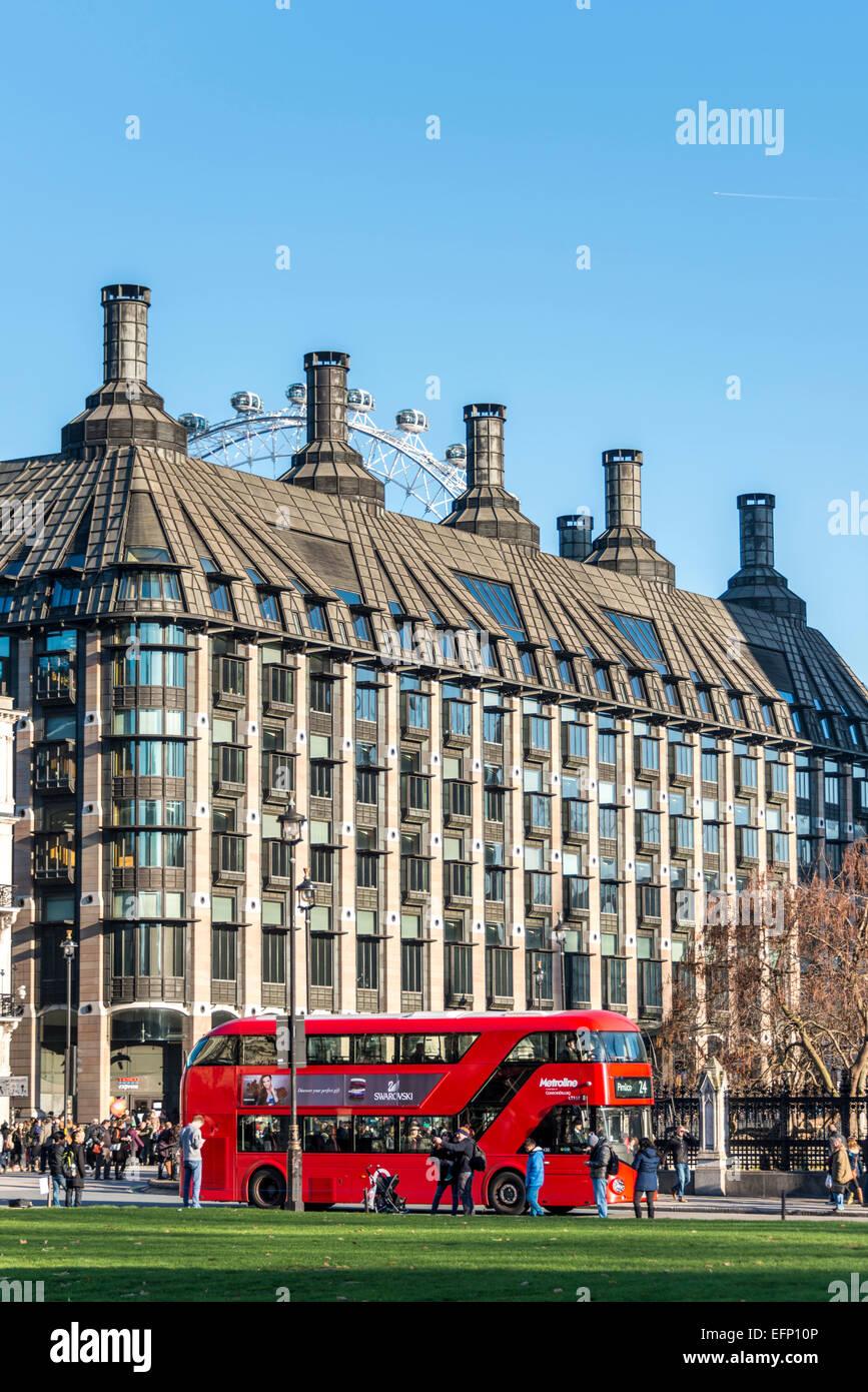 Un autobús rojo de Londres es visto a través de la Plaza del Parlamento, detrás de la cual se Portcullis House y el Ojo de Londres Foto de stock