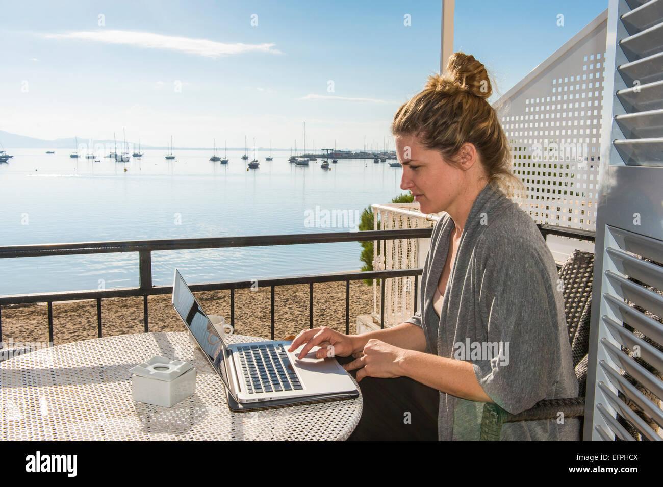 Mujer trabajando en su laptop en un balcón con vistas al océano, Port de Pollença, Mallorca, Islas Imagen De Stock
