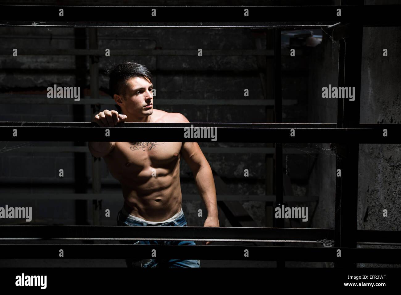 Musculoso descamisado joven apoyado contra la estructura metálica Imagen De Stock