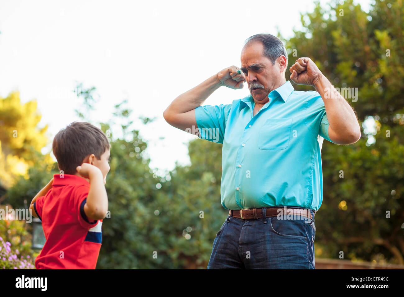 Abuelo y nieto de flexión de los brazos en el jardín Foto de stock