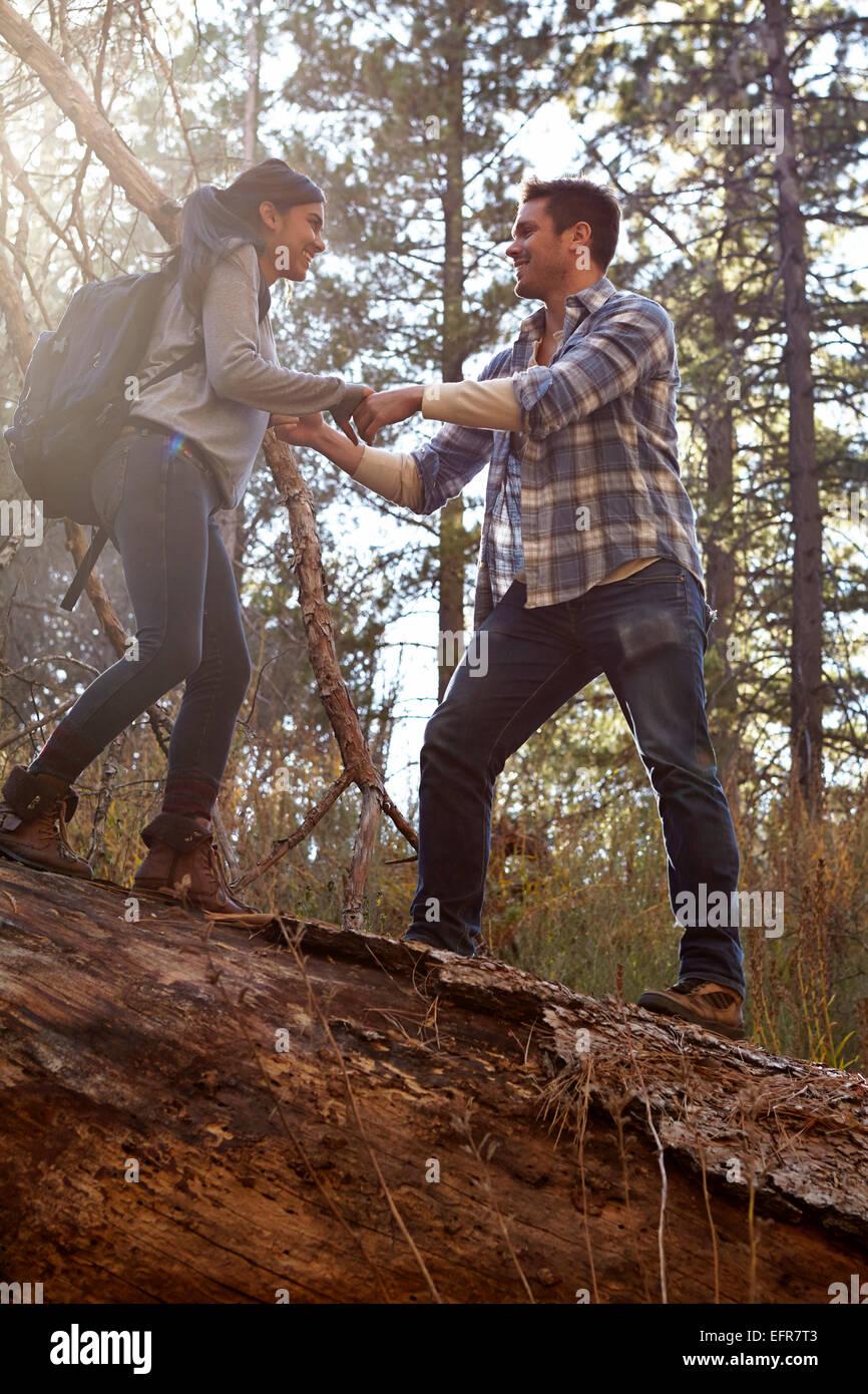 Novia joven dando una mano sobre el árbol caído en el bosque, Los Ángeles, California, Estados Unidos. Foto de stock