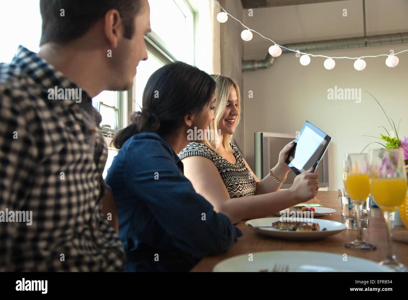 Grupo de amigos a la mesa, mirando la pantalla de Tablet PC digital Imagen De Stock