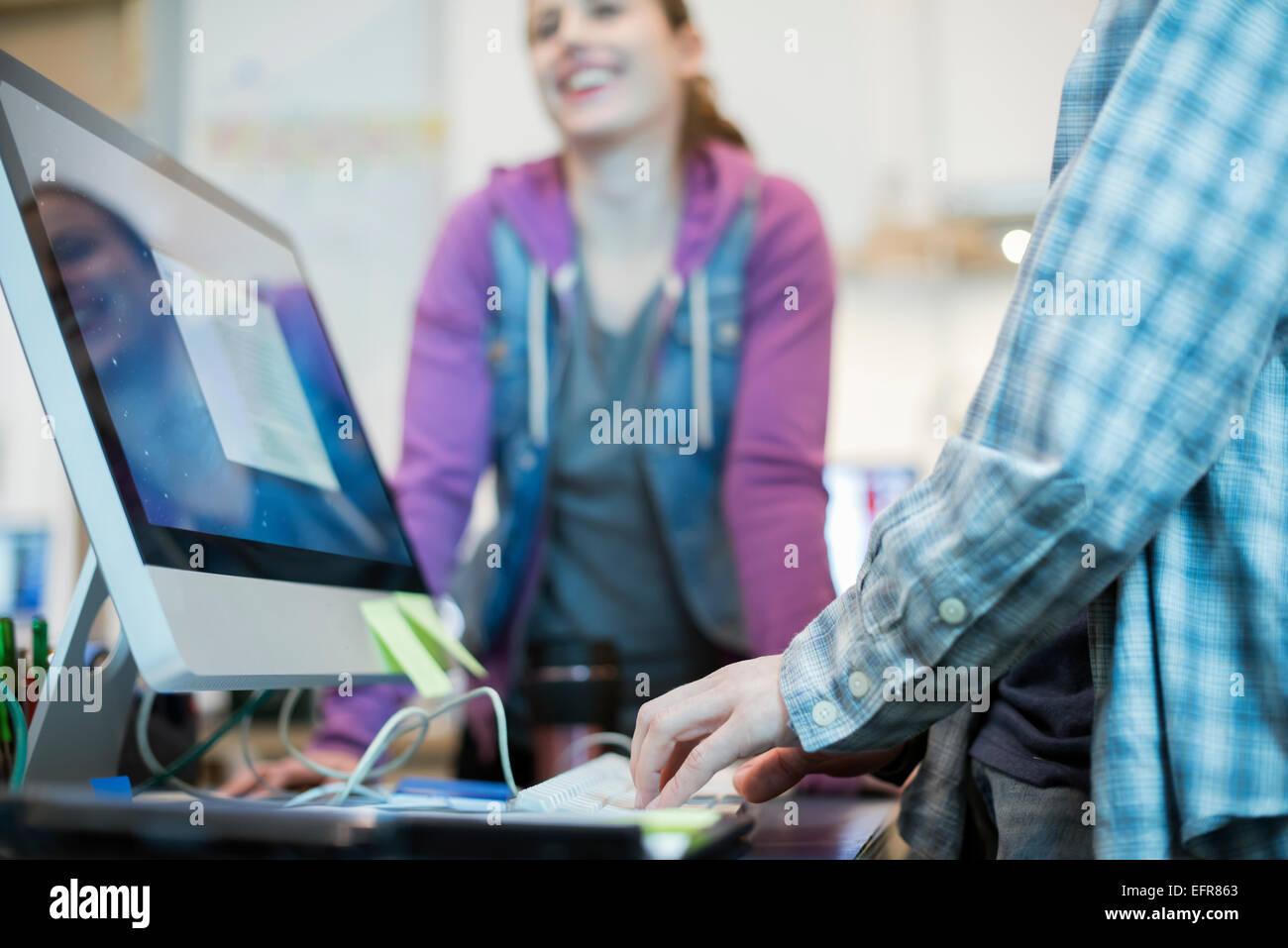 Dos personas en una tienda de reparación de equipo, uno escribiendo y comprobando la pantalla de un monitor. Imagen De Stock