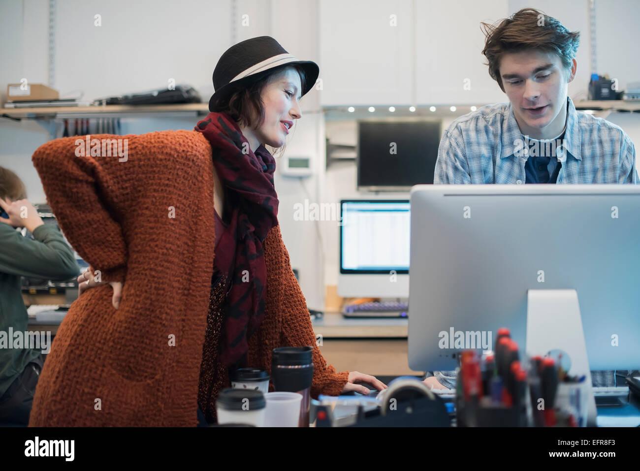 Tienda de reparación de equipo. Un hombre y una mujer hablando de más de un equipo. Imagen De Stock