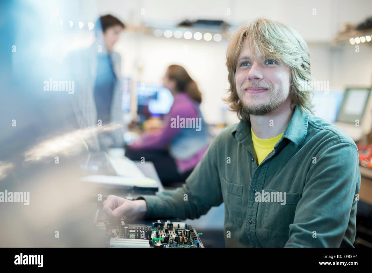 Un hombre joven y dos compañeros de trabajo en una tienda de equipo. Imagen De Stock