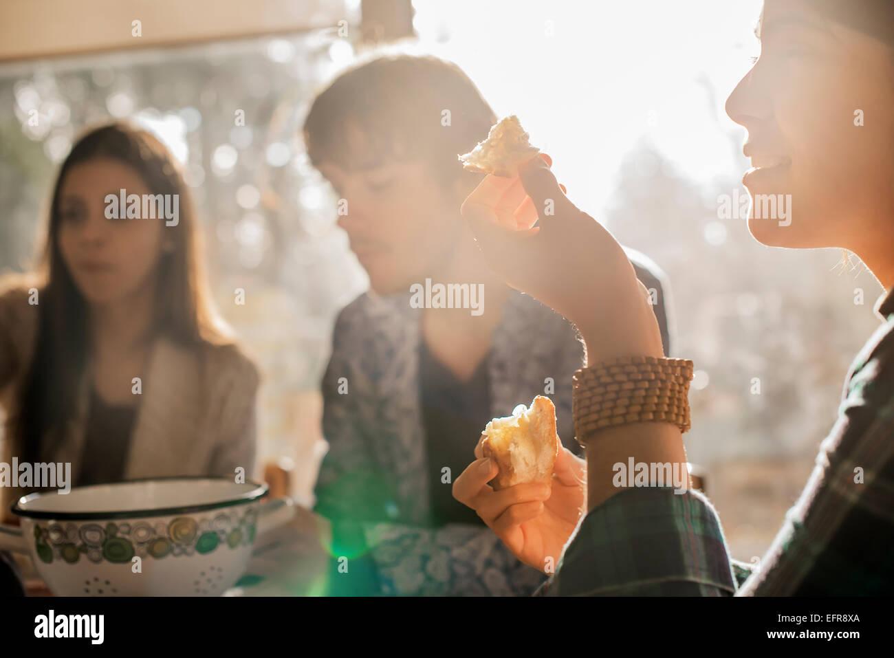 Tres personas sentadas en una mesa, sonreír, comer y conversar. Imagen De Stock