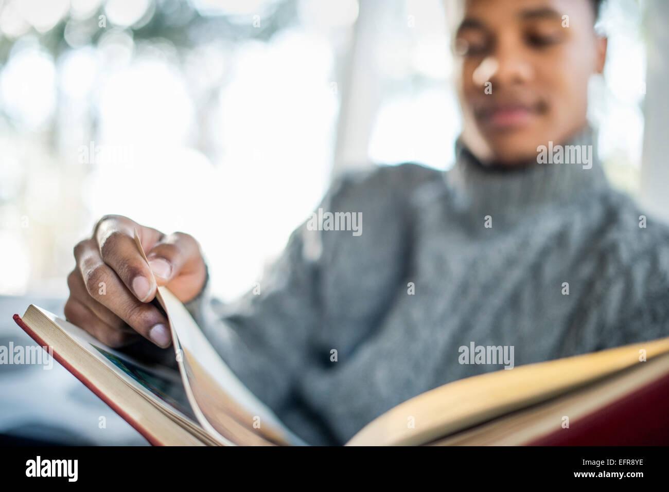 Hombre que llevaba un rollo de puente de cuello gris pasando las páginas de un libro. Imagen De Stock