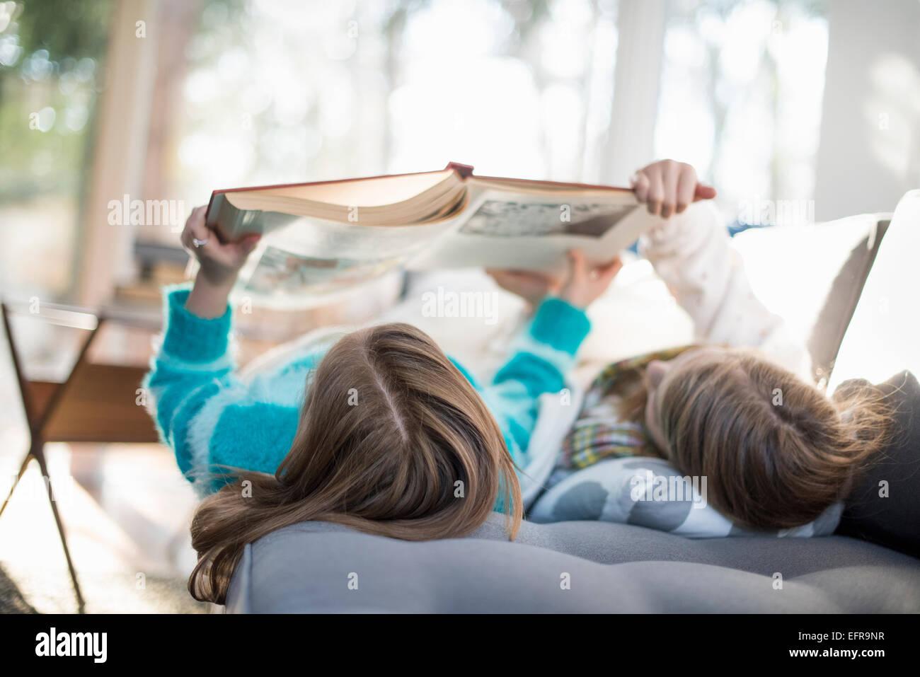 Dos niñas, acostado en un sofá en su espalda, leyendo un libro. Imagen De Stock