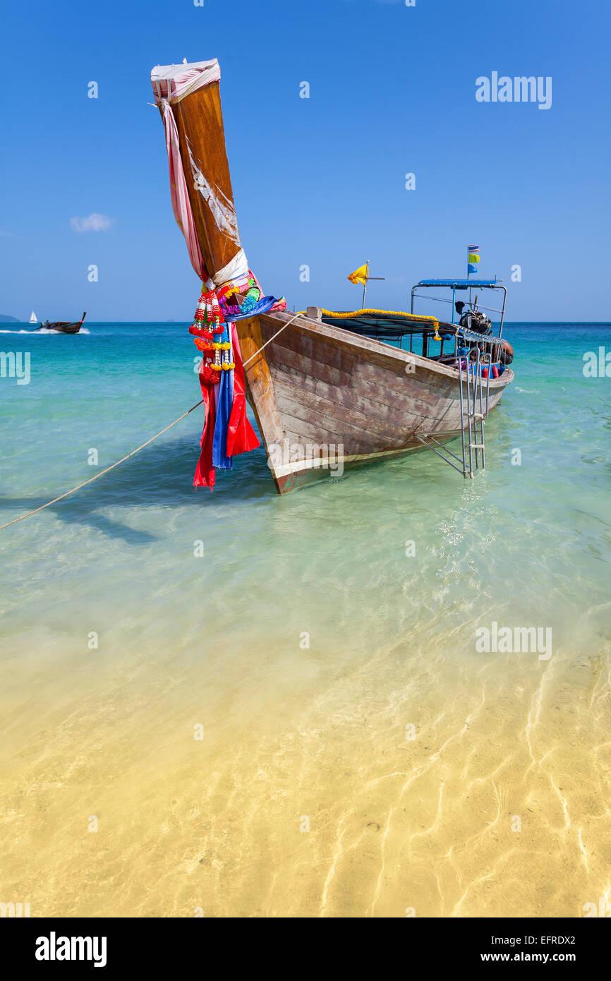 Barco de madera en cristalinas aguas someras, Railay Beach. Foto de stock