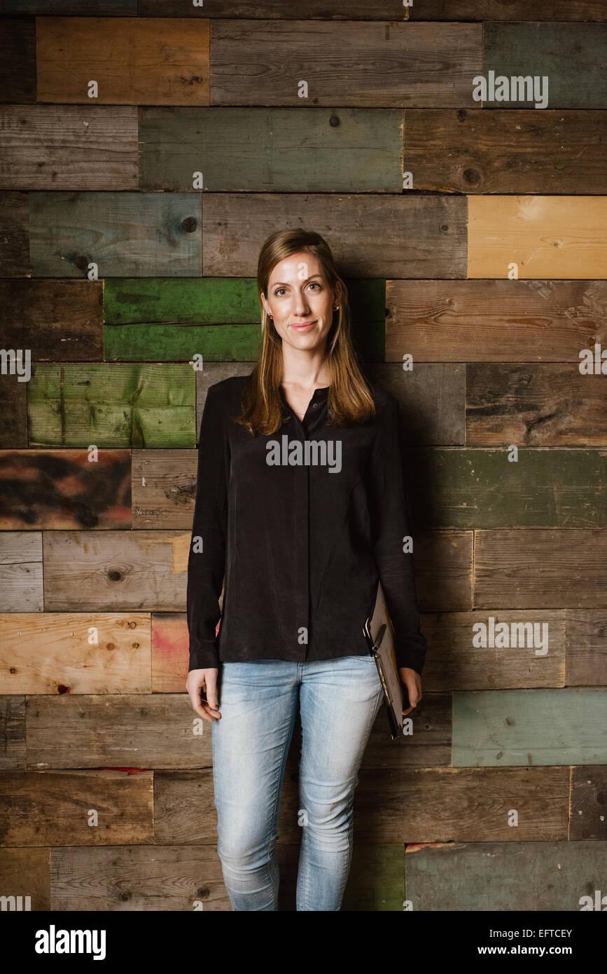 Retrato de mujer joven atractivo de pie contra una pared de madera. Mujer caucásica en casuals en Office mirando Imagen De Stock