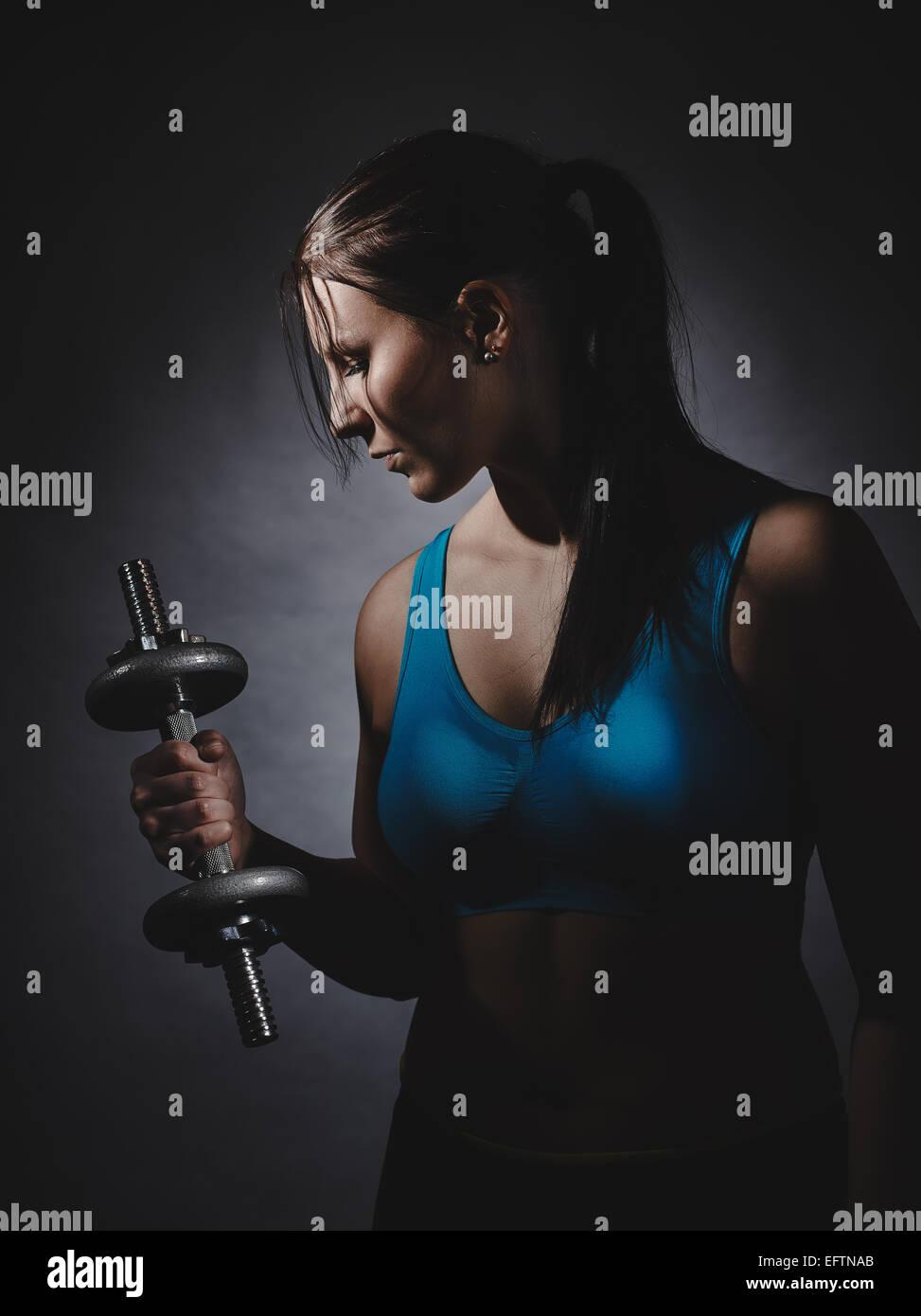 El levantamiento de pesas, la joven mujer vistiendo ropa deportiva y ella ejercer, Foto de estudio, fondo oscuro Imagen De Stock