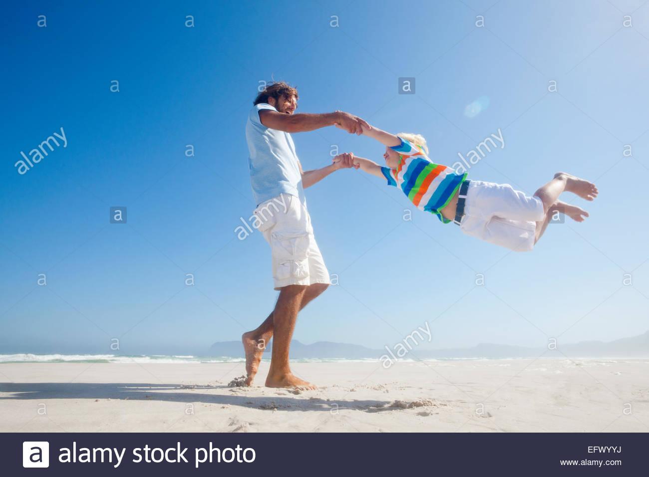 Hijo de padre sonriente oscilando alrededor de alegremente en sunny beach Imagen De Stock
