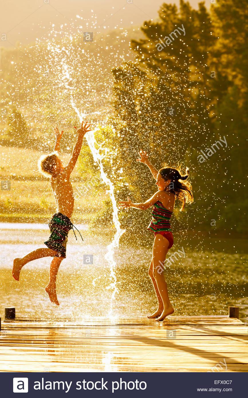 Chico y chica saltar en el aire en el embarcadero a través de salpicaduras de agua Imagen De Stock