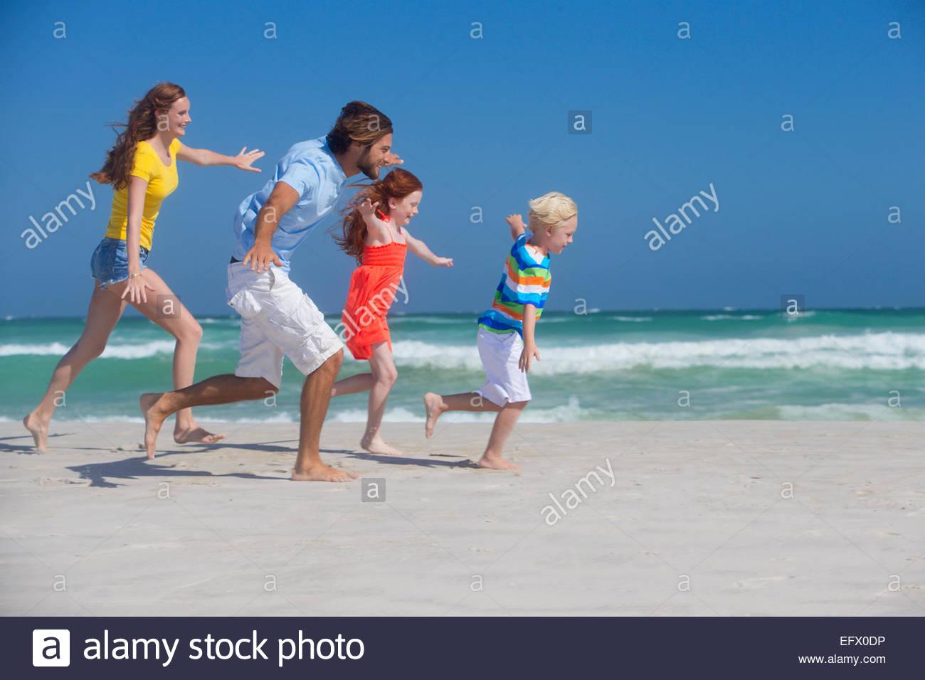 Familia sonriente, pretendiendo volar, ejecutando en sunny beach Foto de stock