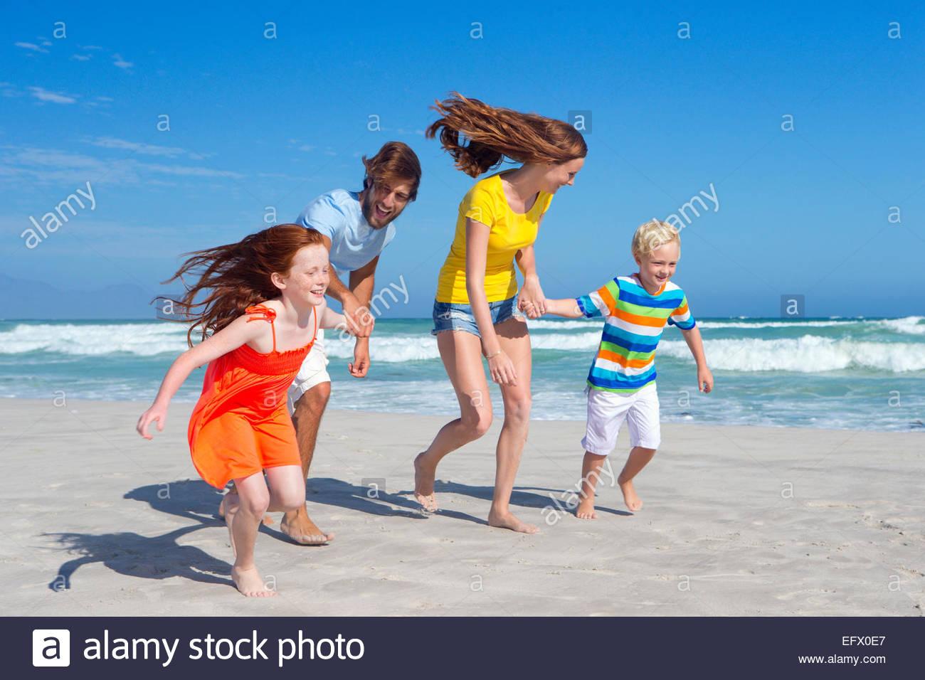 Familia Feliz, tomados de las manos, correr a lo largo de sunny beach Imagen De Stock