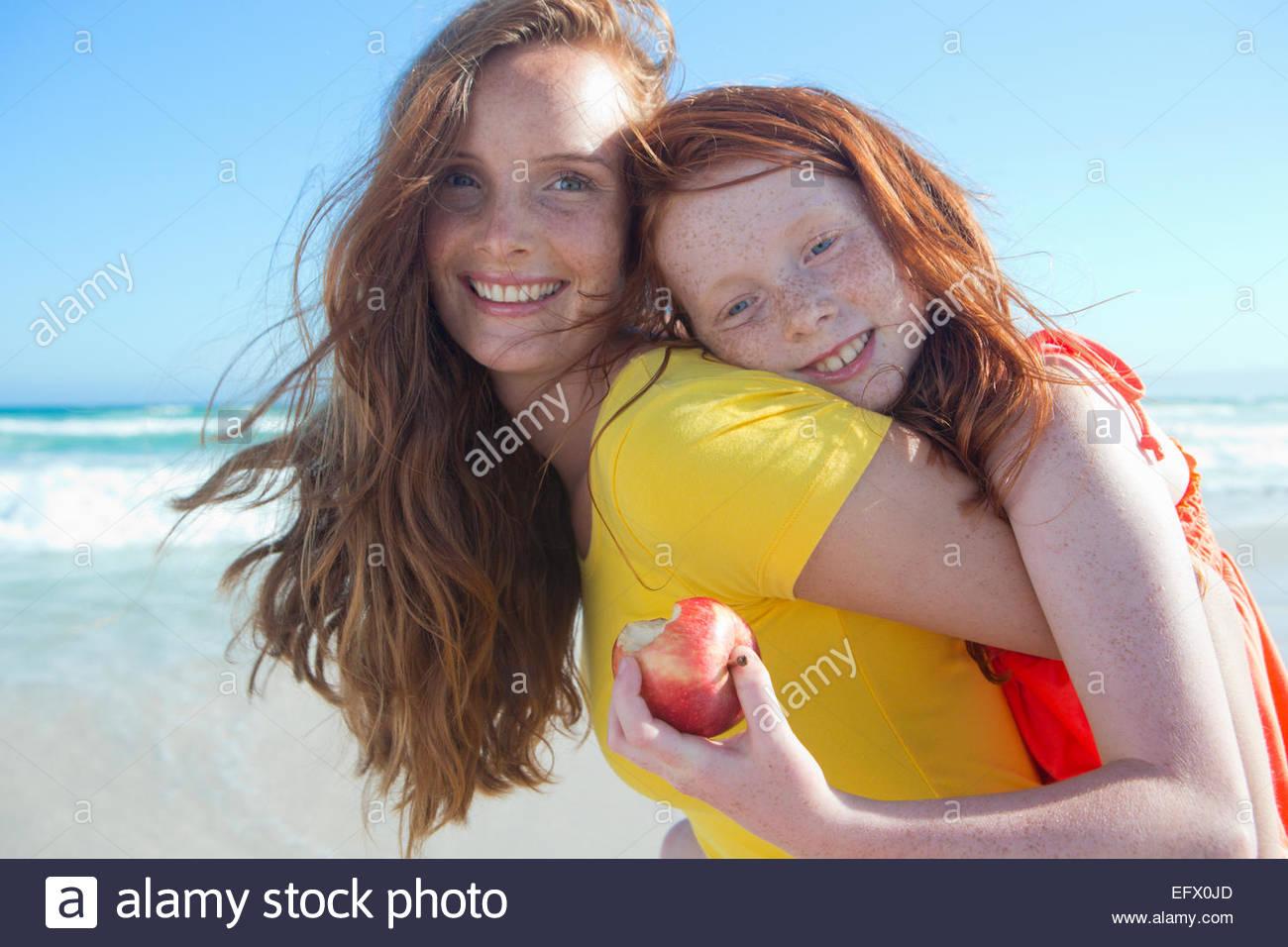 Retrato de niña sonriente Celebración apple, abrazando a la madre, en sunny beach Imagen De Stock
