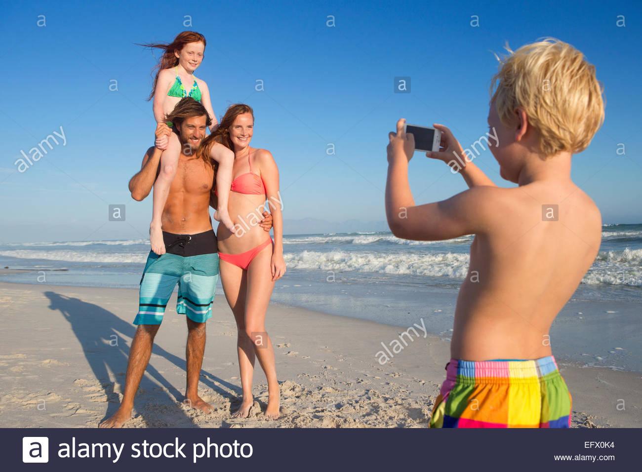 Niño tomando foto de madre, padre y hermana en sunny beach Imagen De Stock