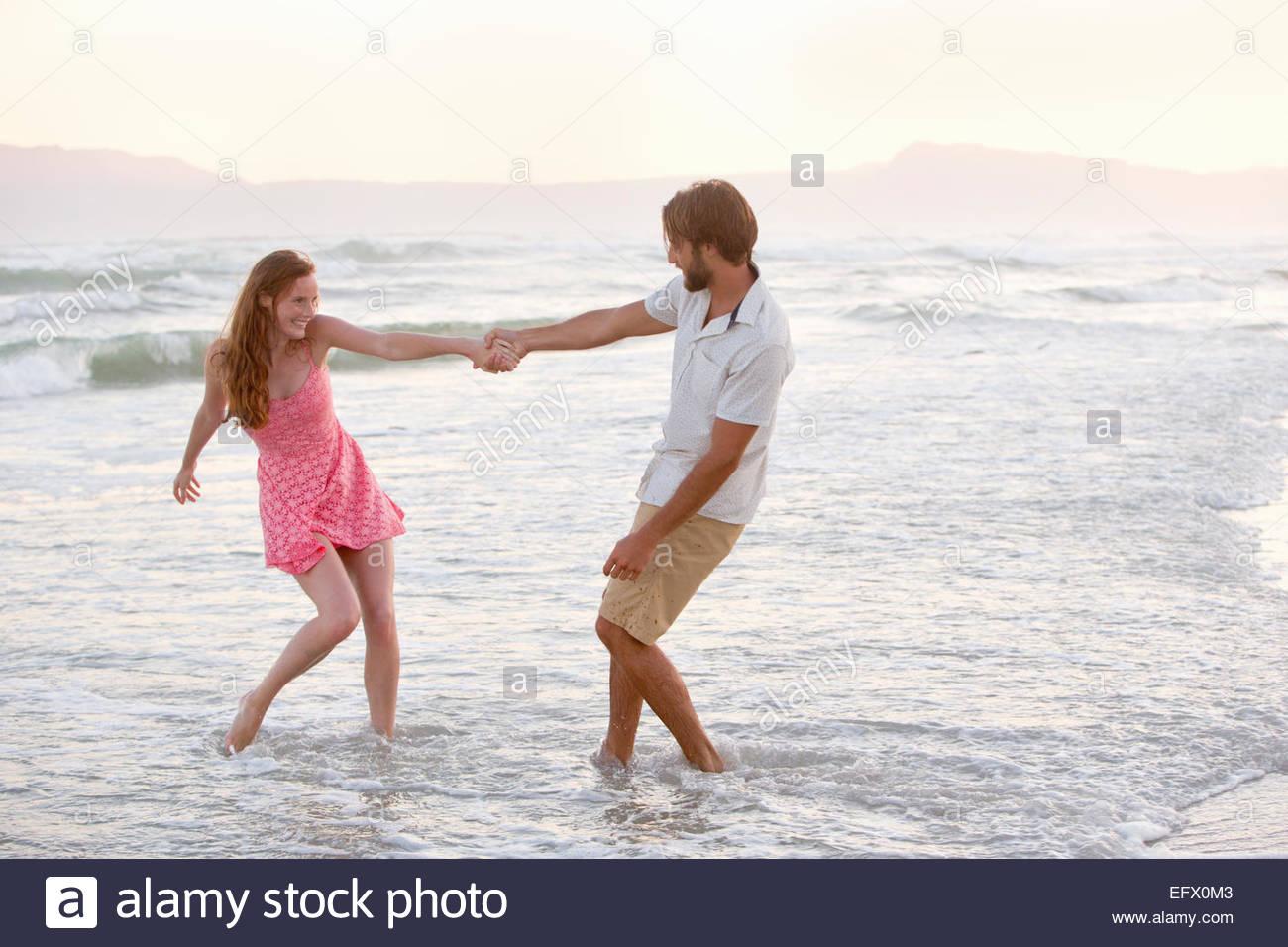 Par, alegremente tirando unos a otros en el mar en sunny beach Imagen De Stock
