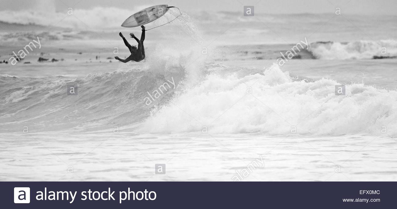 Surfer cayéndose de surf en ola Foto de stock