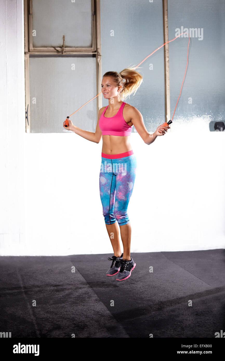 Mujer joven saltando en el gimnasio Imagen De Stock