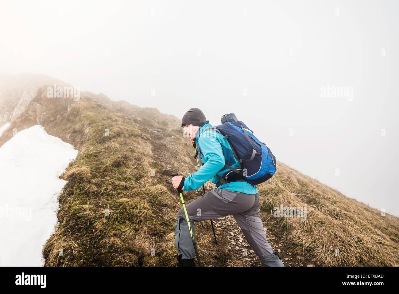 Joven trekking de montaña en nieve y neblina, Alpes bávaros, Oberstdorf, Baviera, Alemania Imagen De Stock