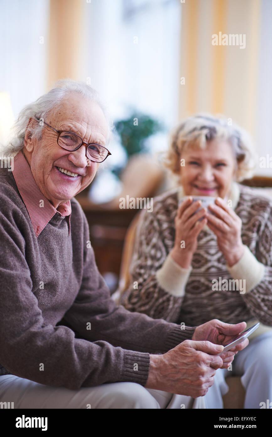 Hombre senior con touchpad mirando a la cámara mientras descansa en su casa los fines de semana Imagen De Stock
