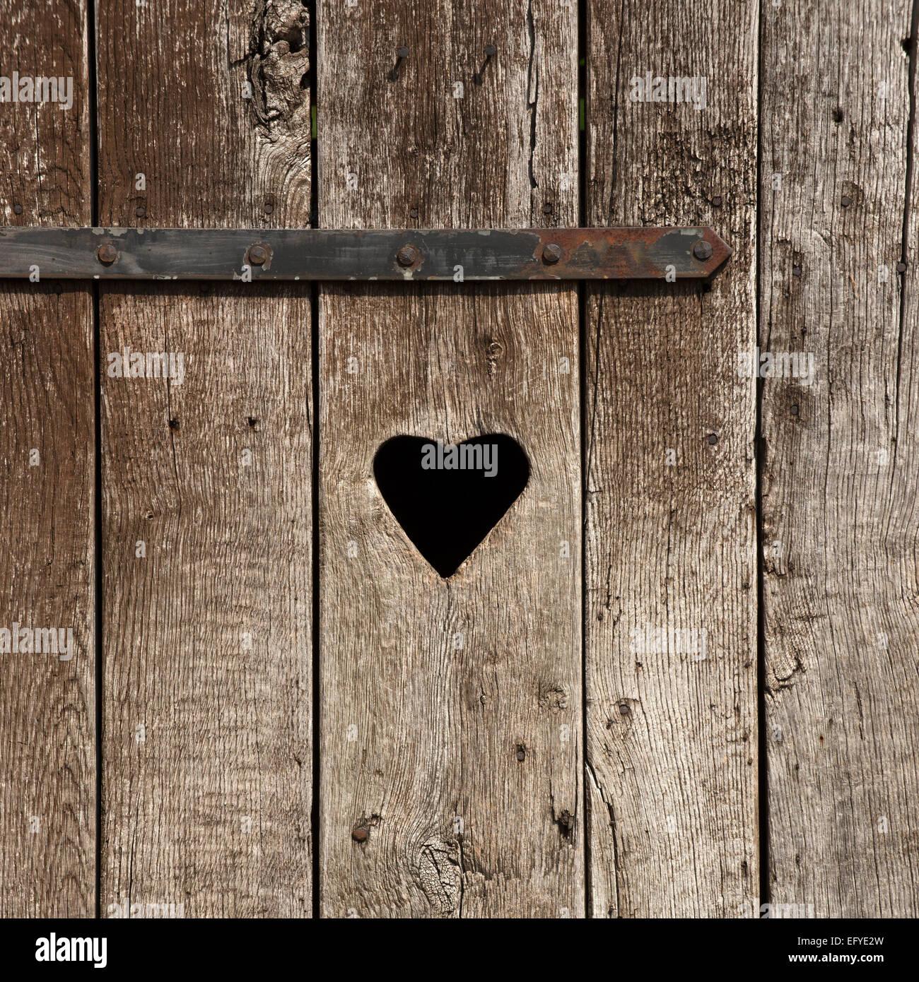 Puerta de madera desgastada con un corazón, baño exterior Imagen De Stock