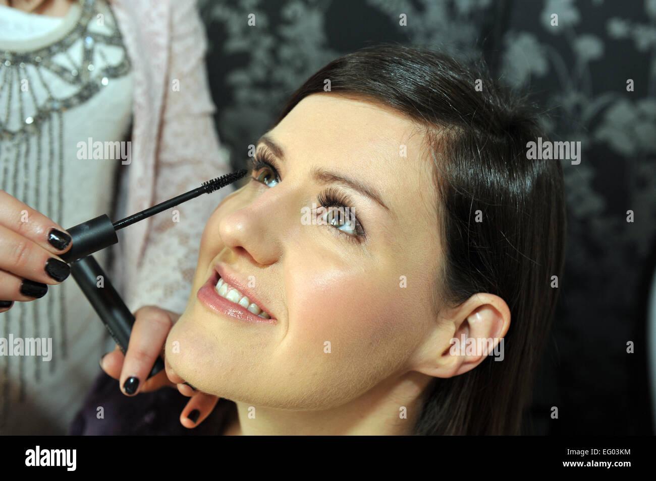 Maquillaje artista aplica la máscara en una mujer joven. Imagen De Stock