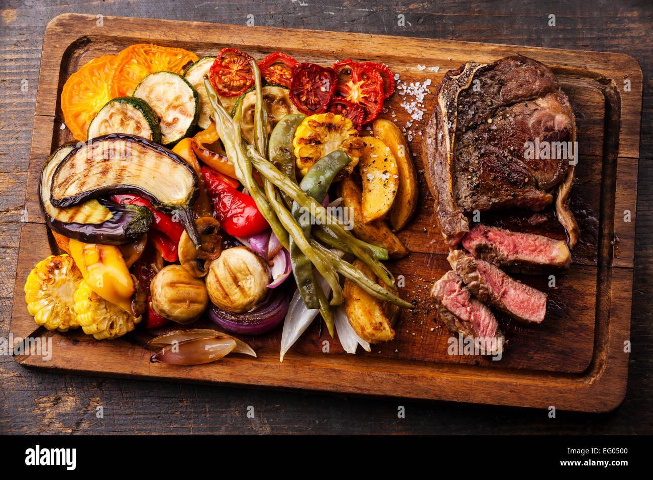 Club de bistec de carne con salsa de pimienta y verduras asadas en placa de corte sobre fondo de madera oscura. Imagen De Stock
