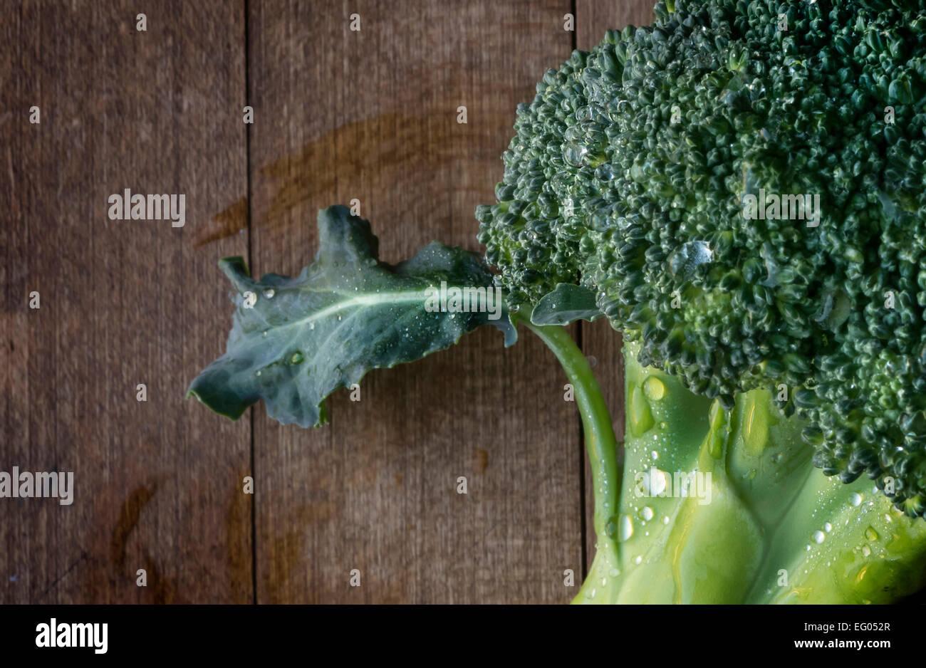 Detalle Macro foto de una floret brocolli con gotas de agua sobre una tabla de cortar de madera Imagen De Stock
