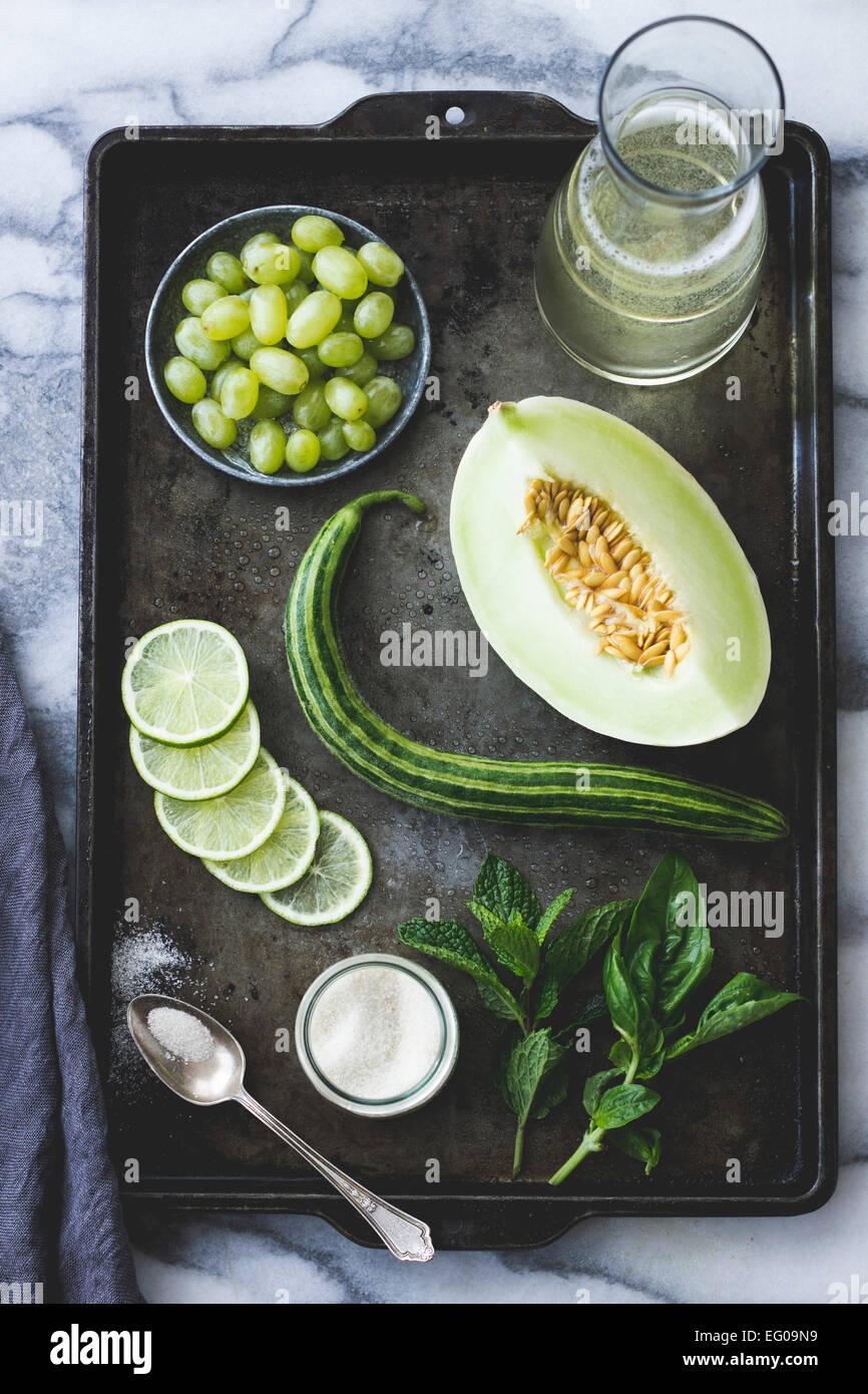 Los Melones, uvas, pepino, menta, azúcar, vinho verde ingredientes en una bandeja para hornear. Imagen De Stock