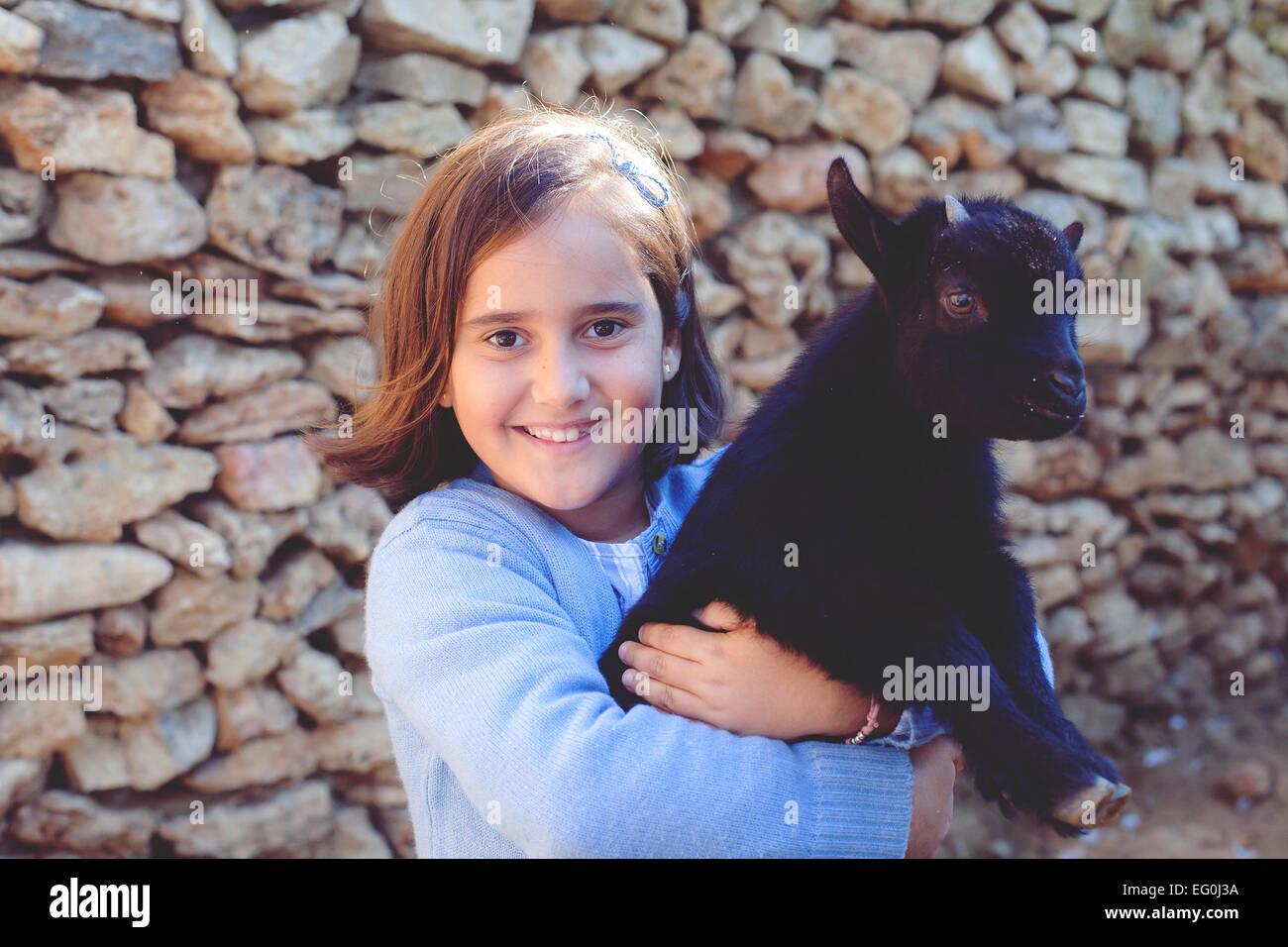Retrato de niña (6-7) con cabrito Imagen De Stock