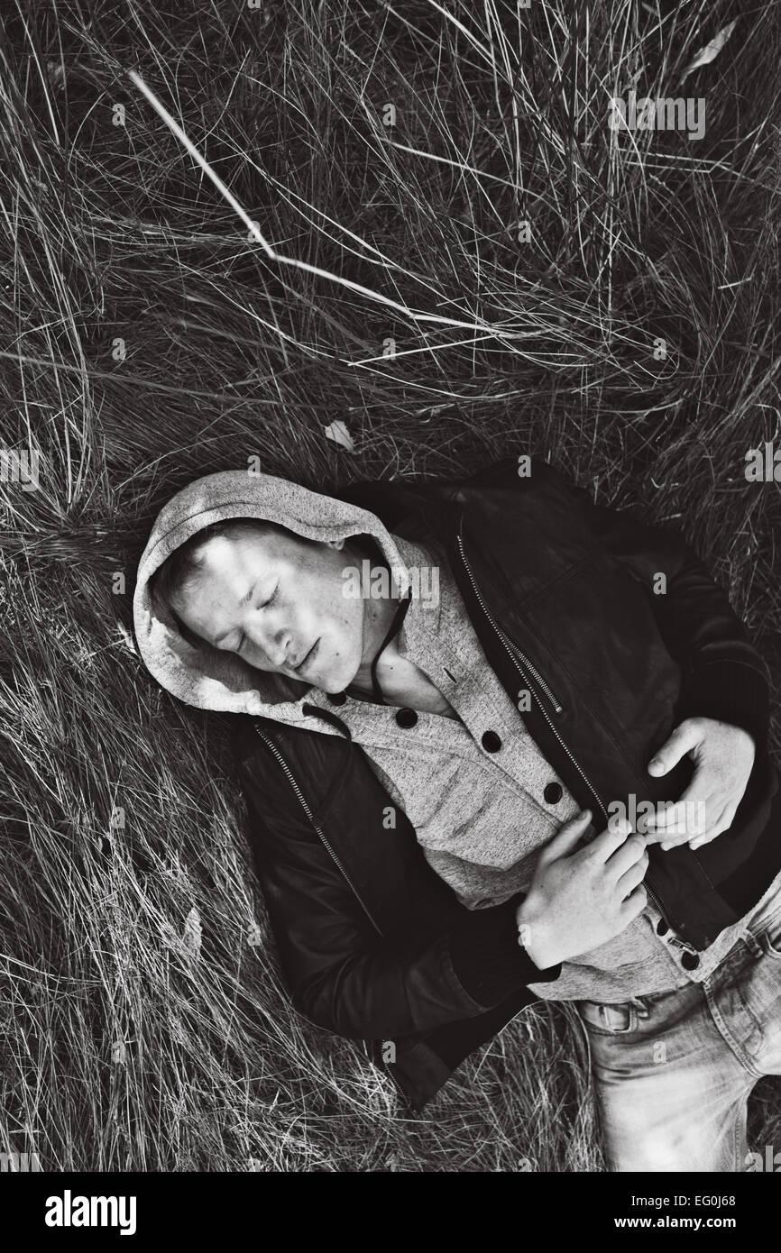 El hombre tumbado en la hierba Imagen De Stock