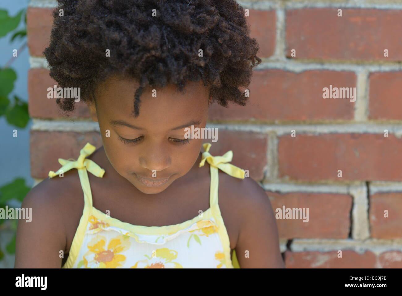 Las niñas de pie junto a una pared de ladrillo mirando hacia abajo Imagen De Stock