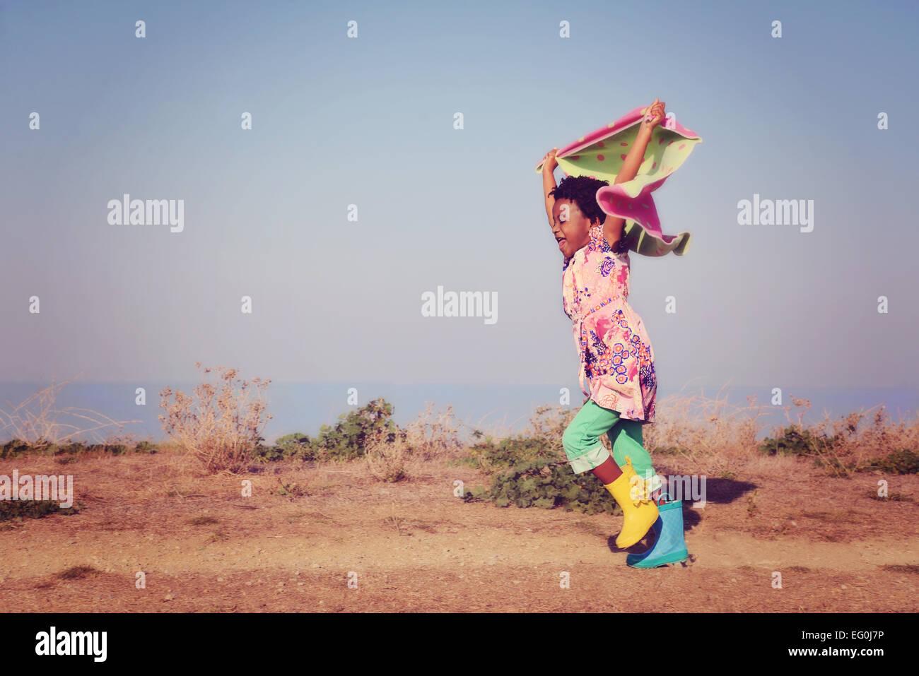 Chica corriendo sujetando la bufanda por encima de su cabeza Imagen De Stock