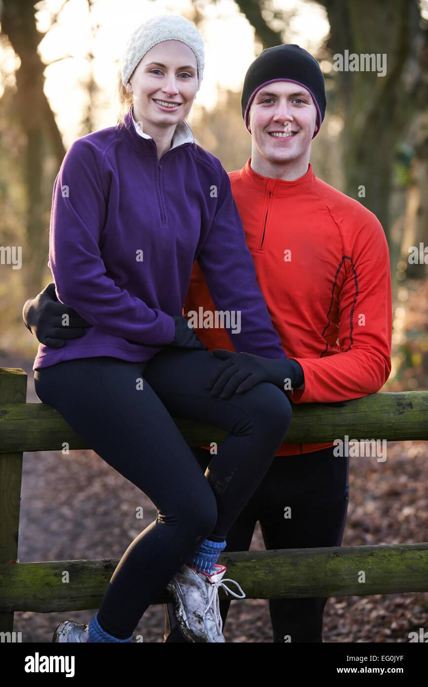 Retrato de pareja en invierno correr a través del bosque sentado en el cerco Imagen De Stock