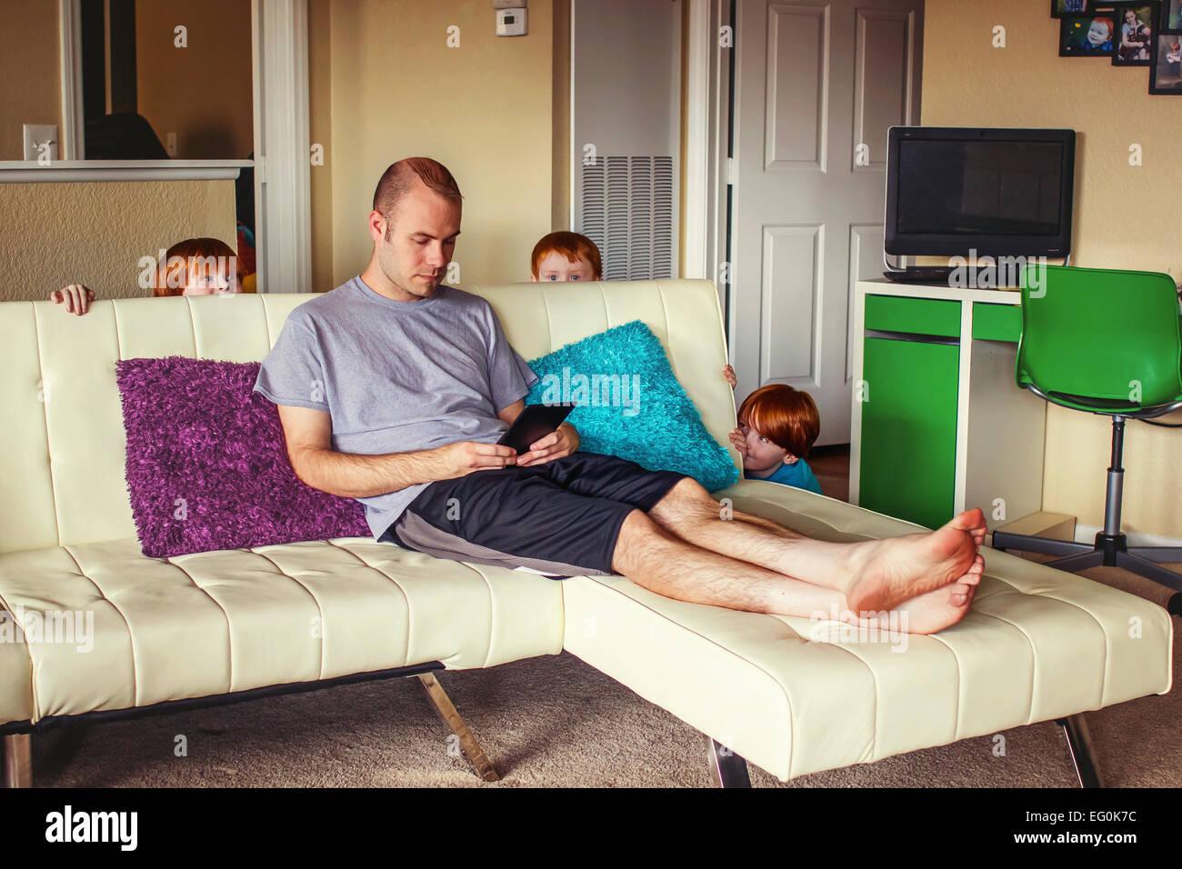 Tres jóvenes escondiéndose detrás del sofá dispuesto a sorprender a su padre Imagen De Stock