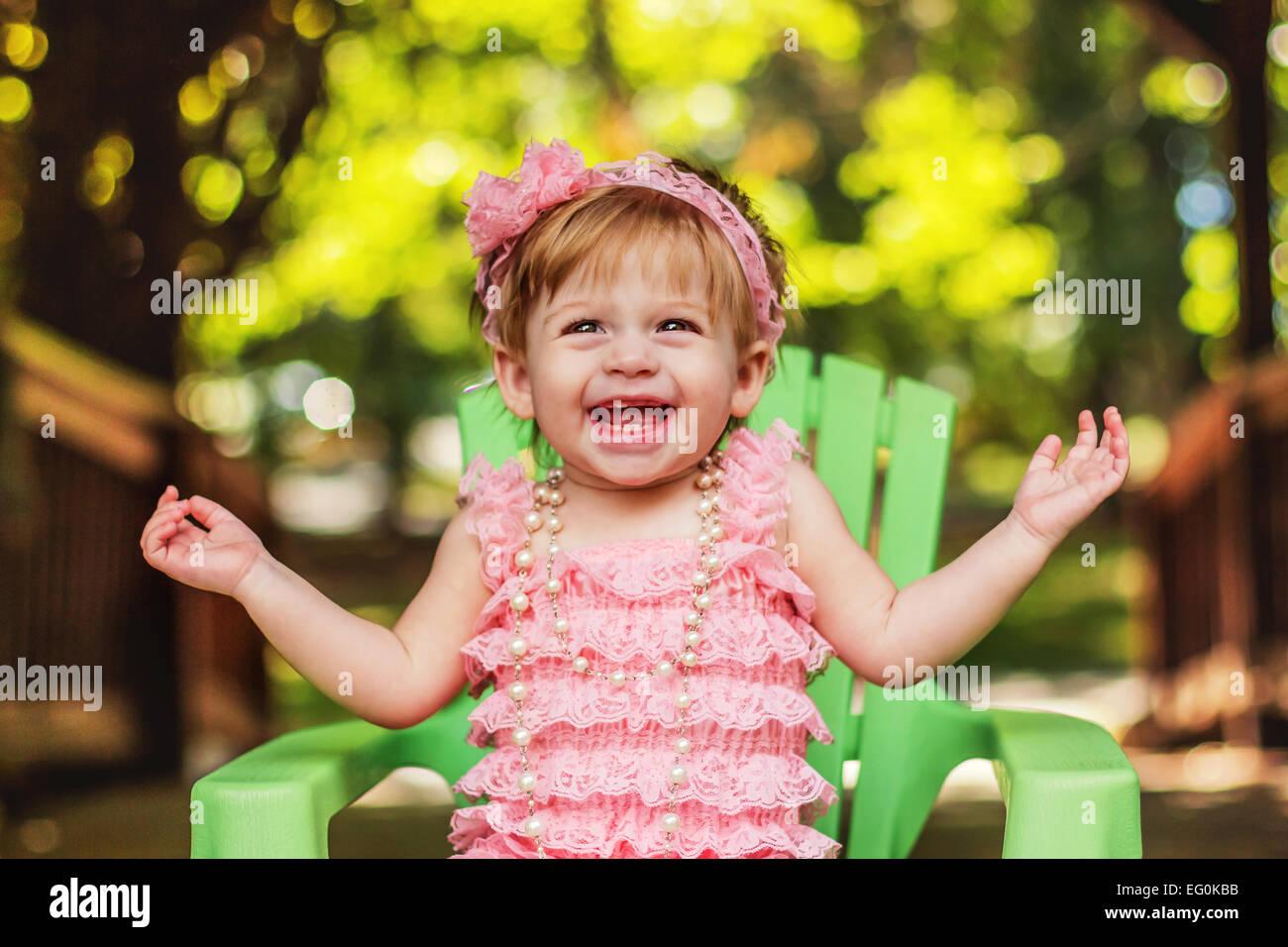 Feliz chica en un vestido de fiesta sentado en la silla de jardín riendo Imagen De Stock
