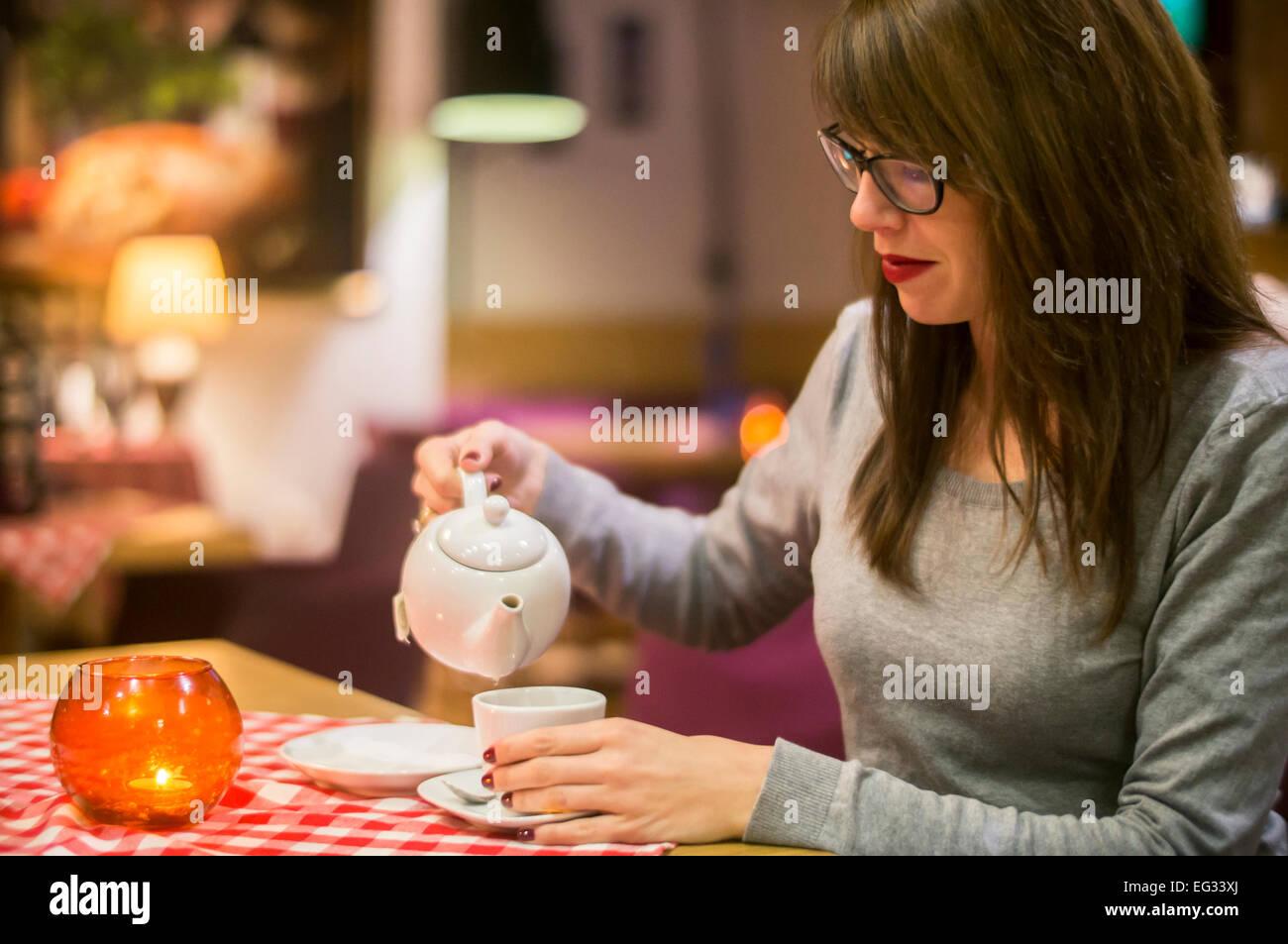 Hermosa joven disfrutando de una bebida caliente con amigos en un acogedor café. Imagen De Stock