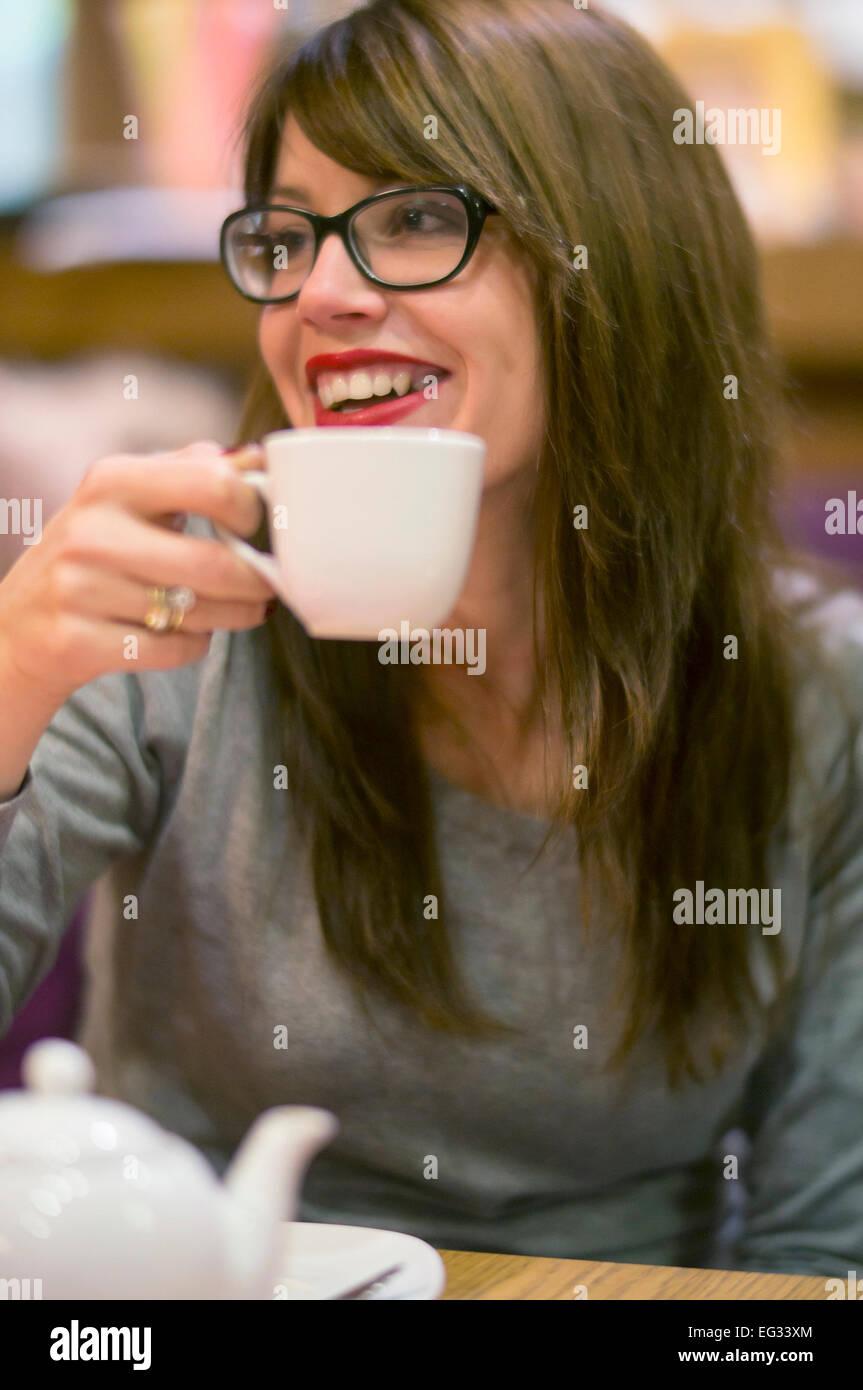 Hermosa joven disfrutando de una bebida caliente con amigos en un acogedor café. Foto de stock