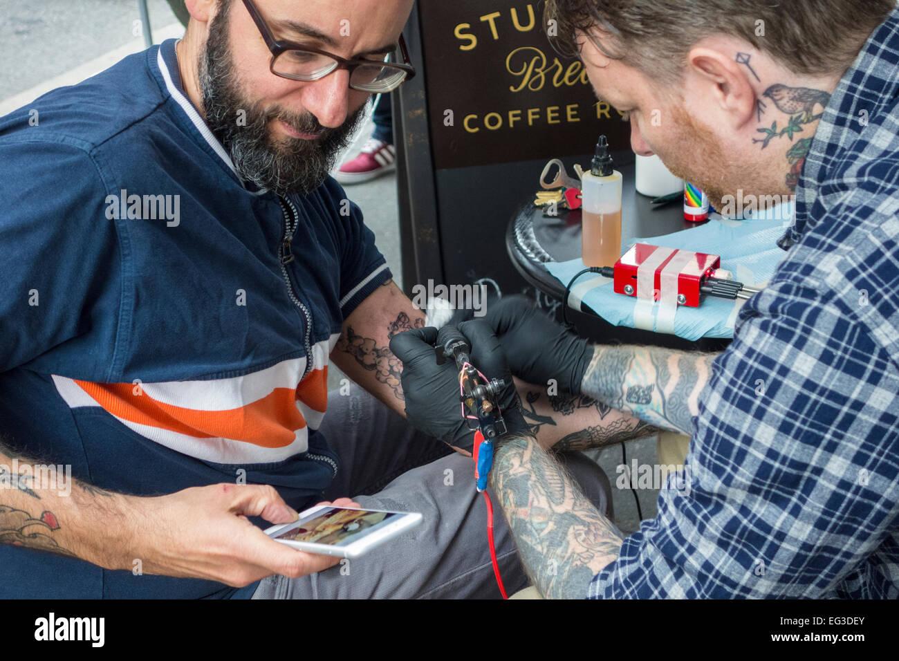 Artista Alex McWatt de tres reyes tatuaje aplicando un tatuaje en el brazo de un hombre que está comprobando su celular Foto de stock