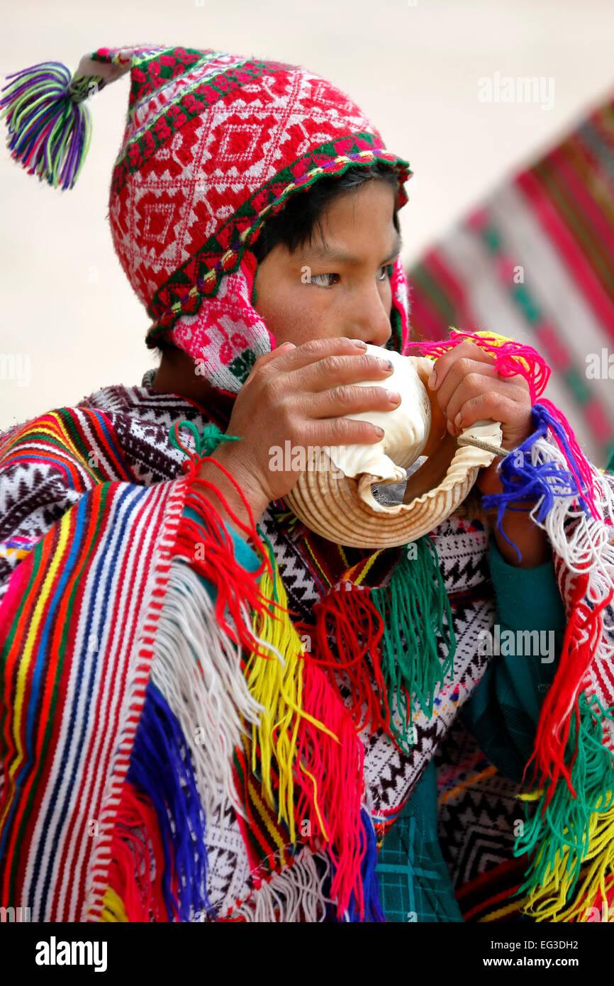 El Quechua muchacho soplando un caracol y vestidos con traje tradicional fuera de la iglesia, Pisac, Cusco, Perú Imagen De Stock