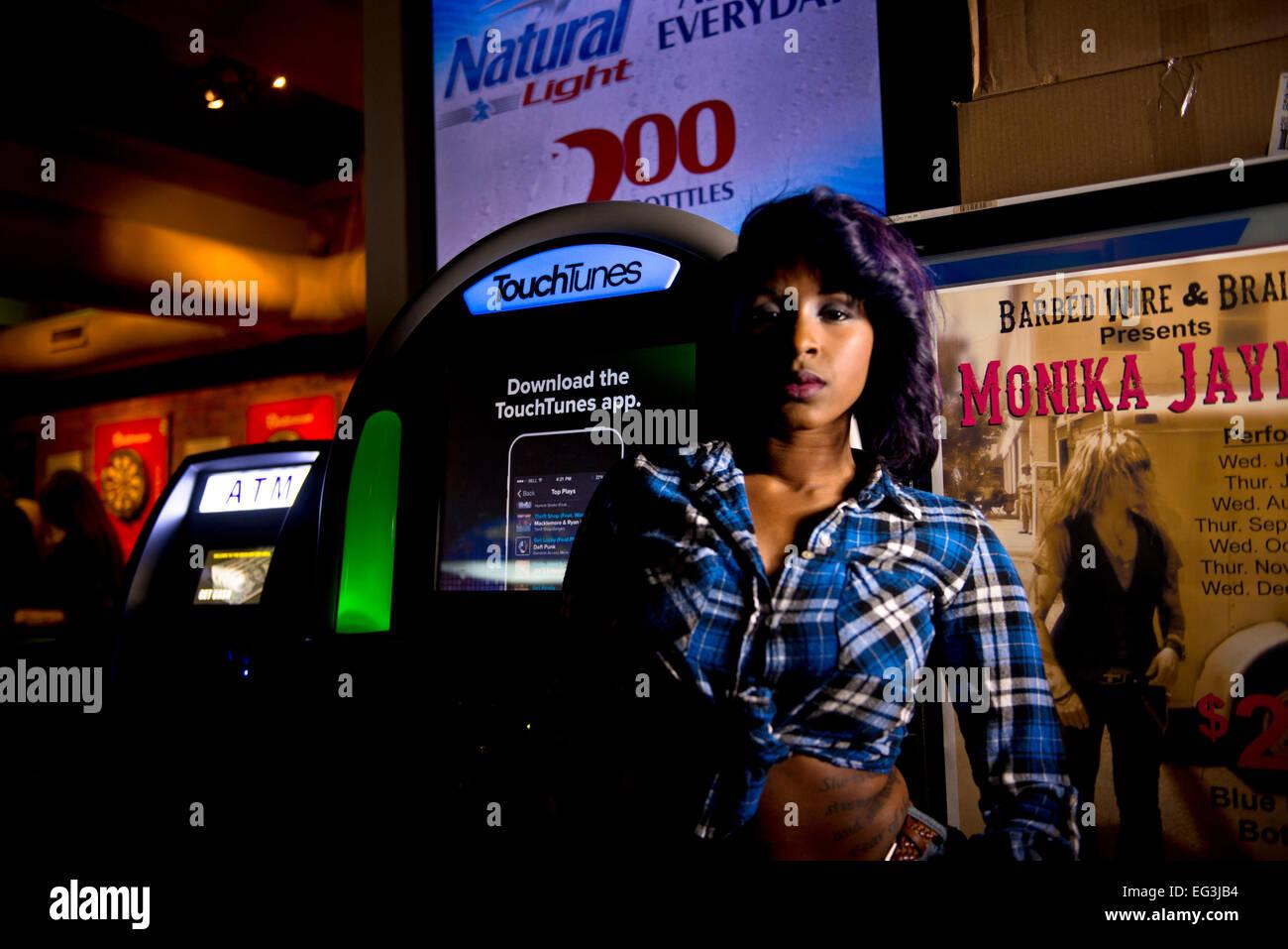 Modelo americano africano de pie por un jukebox en un bar. Imagen De Stock